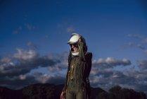 Mujer sonriente en traje de astronauta y casco de pie contra el cielo de la noche en la naturaleza - foto de stock