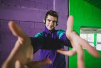 Young man in sportswear and headphones stretching arms to camera — Stock Photo