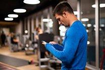 Человек в спортивной одежде с помощью мобильного телефона в тренажерном зале — стоковое фото