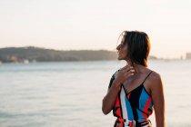 Ragionevole donna elegante in piedi sulla riva al tramonto — Foto stock