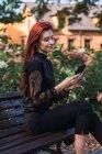 Mujer elegante joven en traje negro de navegación smartphone en el banco en el parque - foto de stock