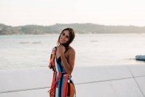 Felice giovane donna in abito colorato in piedi sul lungomare contro pittoresco paesaggio e guardando la fotocamera — Foto stock