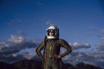 Confiada astronauta de pie en la naturaleza por la noche - foto de stock
