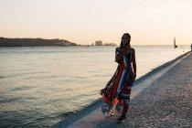 Mujer contenta en vestido largo y colorido caminando en el paseo de adoquines al atardecer contra el paisaje marino - foto de stock