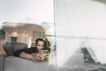 African American man using smartphone on sofa at home — Stock Photo