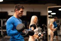 Мужчина в синем свитере и привлекательная женщина в спортивной одежде стоят в спортзале перед зеркалом и делают упражнения с гантелями — стоковое фото