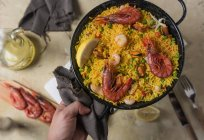 Human hand holding pan of traditional spanish paella marinera with rice, prawns, squid and mussels — Stock Photo