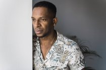 Casual black man leaning on white wall near window — Stock Photo
