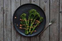 На пару брокколи с romesco соусом на черную листовую вилкой на деревянный стол — стоковое фото