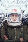 Confident girl wearing old space helmet and spacesuit on foil background — Stock Photo