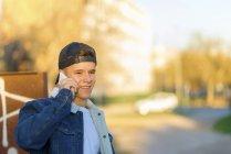 Портрет молодого подростка на улице в повседневной одежде и со смартфоном — стоковое фото