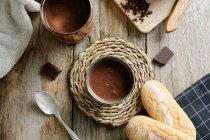 Xícara de chocolate quente com pedaços de chocolate no topo na mesa de madeira — Fotografia de Stock