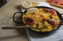 Traditional spanish paella marinera with rice, prawns, squid and mussels in pan — Stock Photo