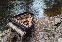 Broken old piano on pavement near lake — Stock Photo