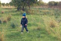 Мальчик гуляет в солнечном парке — стоковое фото