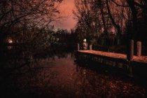 Человек в капюшоне сидит на пирсе у озера между мрачным темным лесом с красным небом в Боске, Раскафрия, Испания — стоковое фото