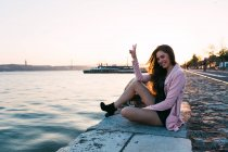 Smiling young woman sitting on embankment near water surface with ship at sunset and showing ok sign — Stock Photo