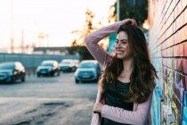 Atractiva mujer joven feliz con mano en posición de pelo en la calle - foto de stock