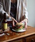 Nahaufnahme einer Frau bei Bier und Veggie-Burger — Stockfoto