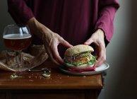 Primer plano de la mujer disfrutando de la cerveza y la hamburguesa vegetariana - foto de stock