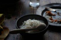Чаша риса и пустая тарелка на деревенском деревянном столе — стоковое фото