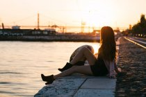 Dreamy sensual young lady sitting on embankment near water surface at sunset — Stock Photo