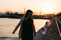 Mujer joven caminando en terraplén cerca de la superficie del agua al atardecer - foto de stock