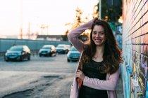 Attrayant jeune femme heureuse avec la main dans les cheveux debout sur la rue — Photo de stock