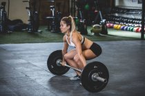 Side view woman in sportswear crouching with barbells with weight plates in gym — Stock Photo