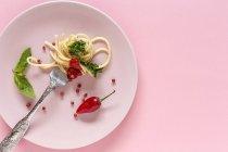 Спагетті з помідорів і песто соус на тарілку, на рожевий фон — стокове фото