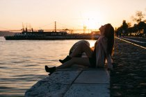 Sensual young woman sitting on embankment near water surface with ship at sunset — Stock Photo
