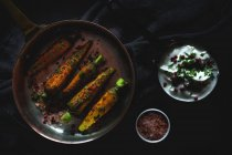 Healthy roasted carrots with herbs and spices on black fabric with sauce — Stock Photo