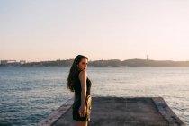 Спокусливі молоду жінку в чорне плаття стоячи на набережній біля поверхні води на заході сонця — стокове фото