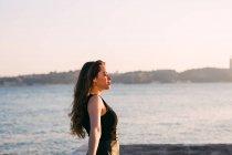 Entspannte, charmante junge Frau in schwarzer Kleidung, die an sonnigen Tagen in der Nähe der Wasseroberfläche steht — Stockfoto