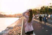 Young woman walking on promenade near water and alley at sunset — Stock Photo