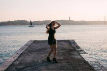 Cheerful woman in black wear and boots dancing on embankment near water surface with yacht at sunset — Stock Photo