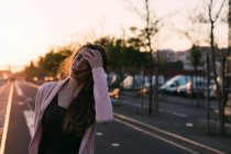 Молодая девушка с рукой в волосы, ходить на аллее на закате — стоковое фото