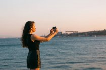Young woman in black dress taking photo with smartphone on embankment near water at sunset — Stock Photo