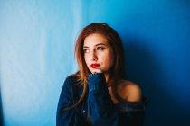 Mujer atractiva de pie cerca de la pared azul - foto de stock