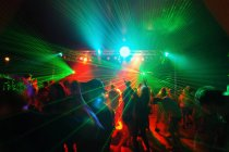 Unrecognizable people on illuminated dance floor — Stock Photo