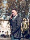 Attraente uomo adulto in giacca elegante tenere la mano in tasca e distogliere lo sguardo pur avendo conversazione smartphone — Foto stock