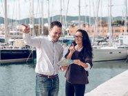 Beau geste d'homme adulte avec la main et tenant la carte tout en montrant la voie à touriste féminine dans le port — Photo de stock