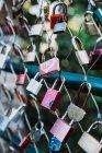 Bando de vários cadeados de amor pendurados na cerca líquida no fundo desfocado do parque verde — Fotografia de Stock
