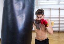 Junge bärtigen Kerl training im Fitnessraum mit Boxsack — Stockfoto