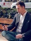 Красивый взрослый мужчина в элегантной куртке держит смартфон и смотрит в сторону, сидя на скамейке на улице — стоковое фото