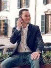 Bonito homem adulto na jaqueta elegante segurando smartphone e olhando para longe enquanto sentado no banco na rua — Fotografia de Stock