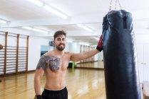 Портрет усміхнений молодих боксер, спираючись на удар сумка в тренажерний зал — стокове фото