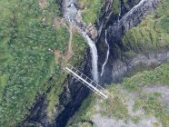 Bridge over spectacular ravine and waterfall in nature — Stock Photo