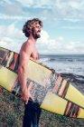 Sonriente tipo de pie con tabla de surf brillante en la costa cerca del océano con tabla de surf - foto de stock