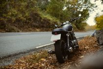 Cafe racer motorbike parked on road in autumn countryside — Stock Photo